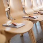 Row of chairs with notebook and pens on top